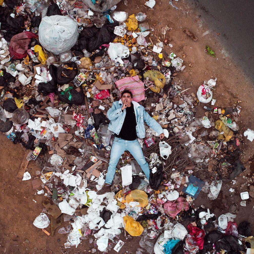 contaminacion basura polución mar plástico hombre acostado sobre basura propuestas para combatir el cambio climático